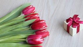 des tulipes et le cadeau blanc rouge avec l'arc rouge sont situés sur une table blanche banque de vidéos