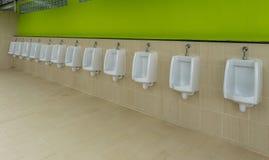 Des urinoirs sont alignés sur le mur Images stock