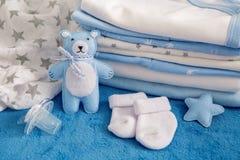 Des vêtements de bébé avec des couches-culottes sont empilés image libre de droits