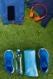 Des vêtements de sport bleus, une bouteille de l'eau et des accessoires pour la forme physique, sont arrangés dans une rangée dan Images stock
