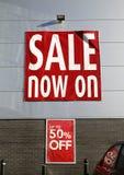 Des Verkaufs auf- große rote Plakatwerbung jetzt ein Verkauf mit 50% Reduzierungen Stockbild