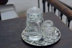 Des verres de l'eau sont placés sur un plat Photo libre de droits