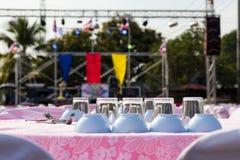 Des verres et les tasses sont placés sur la table devant l'étape Photographie stock libre de droits