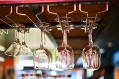 Des verres pour le vin et martini sont accrochés sur le compteur de barre par un café brouillé de fond photos stock