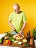 Des von mittlerem Alter frischer Salat Mannkochs Stockfoto