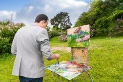 Des von mittlerem Alter mischende Farben modernen männlichen Malers Stockbild