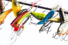 Des wobblers colorés d'appât soient suspendus sur le blanc du ` s de tige Photographie stock libre de droits