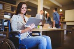 Desabilitou a mulher de negócios nova que usa a tabuleta digital fotografia de stock royalty free
