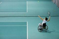 Desabilitou a mulher madura na cadeira de rodas que joga o tênis no campo de tênis Fotos de Stock Royalty Free