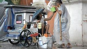 Desabilitou na cadeira de rodas e o homem cego implora sob a chuva vídeos de arquivo