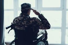Desabilitou na saudação uniforme militar na cadeira de rodas imagem de stock royalty free