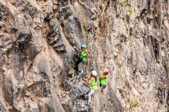 Desafio Al Basalto de通古拉瓦火山,攀登岩石墙壁的小组登山人 库存图片
