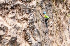 Desafio Al Basalto de通古拉瓦火山,攀登岩石墙壁的少年女孩 库存图片
