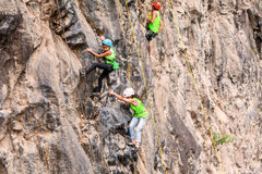 Group Of Teenager Climbers Climbing A Rock Wall Stock Photo