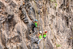 Group Of Courageous Climbers Climbing A Rock Wall Stock Image