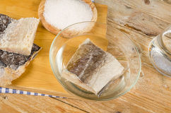 Desalting cod. Several pieces of dried cod being desalted in fresh water royalty free stock photos