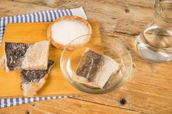 Desalting cod. Several pieces of dried cod being desalted in fresh water stock images