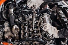 Desaparafusa a porca com a ferramenta Repara??o do motor diesel, das m?os dos trabalhadores e da ferramenta modernos foto de stock royalty free