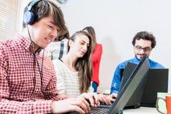 Desarrollador en la compañía de lanzamiento de las TIC que programa en la PC Fotos de archivo
