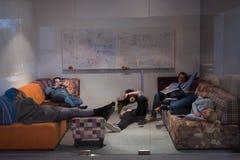 Desarrolladores de software que duermen en el sofá en oficina de lanzamiento creativa fotos de archivo libres de regalías