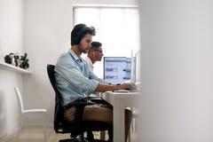 Desarrolladores de uso que trabajan en los ordenadores en oficina foto de archivo