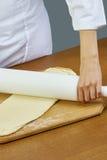 Desarrolle la mano del primer de la pasta del panadero del cocinero en pizza azul uniforme del cocinero del delantal en la colecc Fotos de archivo libres de regalías