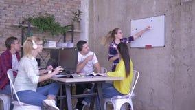 Desarrollo de negocios, gente de la oficina en la tabla que escucha un colega cerca del whiteboard y hacer notas en cuadernos metrajes