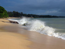 Desaru beach with breaking waves. Untrodden sandy beach with sea waves breaking over large rocks at Desaru, Johor, Malaysia stock image