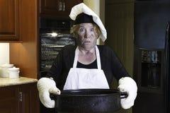 Desastre da cozinha com o chapéu do avental e do cozinheiro chefe Foto de Stock