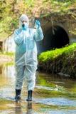 desastre ecológico do conceito, cientista ambiental com uma amostra contaminada de água do esgoto foto de stock
