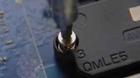 Desatornillar el tornillo Una mano que sostiene un destornillador es de instalación o de reparación de componentes de ordenador metrajes