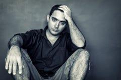 Desaturated beeld van een beklemtoonde en ongerust gemaakte jonge mens Stock Afbeelding