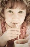 Desaturated Bild von oung Mädchen mit dem gelockten roten Haar trinkend durch ein Stroh Stockfotografie