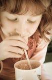 Desaturated Bild von oung Mädchen mit dem gelockten roten Haar trinkend durch ein Stroh Lizenzfreie Stockfotografie