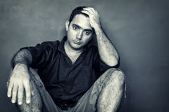 Desaturated  image of a stressed and worried young man. Grunge desaturated  image of a stressed and worried young man sitting on the floor isolated on a black Stock Image