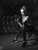 Desaturated photo of sports woman with dumbbell Stock Image