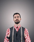 Desaturated portrait of young bearded hipster with hands pushed in his vest Royalty Free Stock Photos