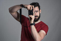 Desaturated stående av fotografen som tar fotoet med dslrkameran som vertikalt rymmer Arkivfoton