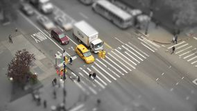 Desaturated tilt shift aerial view of a city intersection stock video