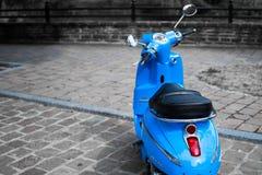 Desatured obrazek błękitna hulajnoga Peugeot Django parkujący w ulicie klasyczny vespa lub obraz royalty free