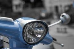 Desatured schließen oben vom Scheinwerfer eines blauen klassischen Roller Vespa mit defocused Hintergrund lizenzfreie stockfotografie