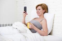 Desayunar el coffe en cama mientras que mira noticias de Internet en su teléfono móvil en la comunicación en línea Foto de archivo