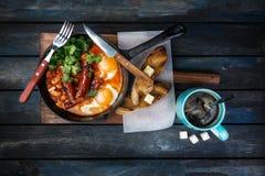 Desayune adentro en un sartén caliente con los huevos fritos, las salchichas, las habas, el verdor y las tostadas Con café azúcar imagen de archivo