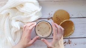 Desayune con el capuchino y los buñuelos hechos en casa en una tabla de madera - 2 Las manos del ` s de la muchacha tuercen una t metrajes