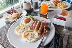 Desayune con el huevo frito, jamón, salchicha, ensalada, zumo de naranja Imagen de archivo