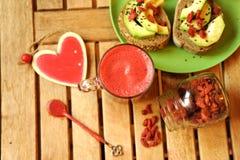 Desayune con el zumo de fruta, las semillas del goji y el bocadillo del aguacate Fotografía de archivo libre de regalías