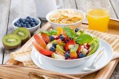 Desayune con la ensalada de fruta, los copos de maíz y el zumo de naranja Fotos de archivo libres de regalías