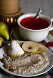 Desayune con las gachas de avena, la pera y el té de las bayas Foto de archivo libre de regalías