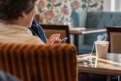 Desayune con los amigos, los teléfonos móviles, y una taza caliente de té imagenes de archivo