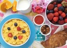 Desayune con los copos de maíz, la leche, los cruasanes, el atasco, las frutas frescas y las almendras Imagen de archivo libre de regalías